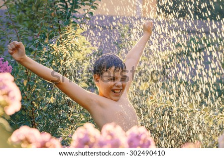 Summer fun. Excited 11-years boy enjoying water shower in the garden. Water drops in sunlight.