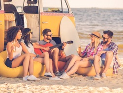 Summer fun. Group of joyful young people drinking beer and playing guitar while sitting on the beach near their retro minivan