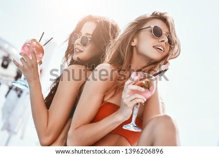 Summer fun has begun. Girls sitting by the pool, drinking cocktails Zdjęcia stock ©