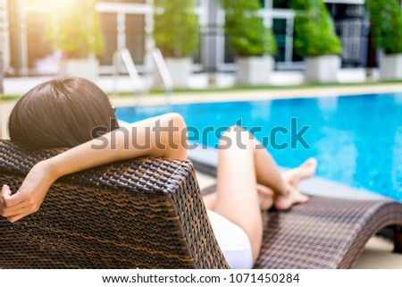 Summer fun in holiday, Happy beautiful woman relaxing sunbathe near luxury swimming pool, summer holiday vacation concept. #1071450284