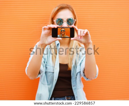 Summer, fun, technology and people concept - cool girl makes self-portrait on the smartphone outdoors against colorful wall
