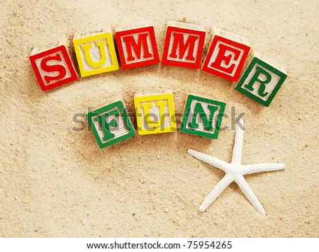 summer fun written in colorful wooden blocks on a beach with a starfish