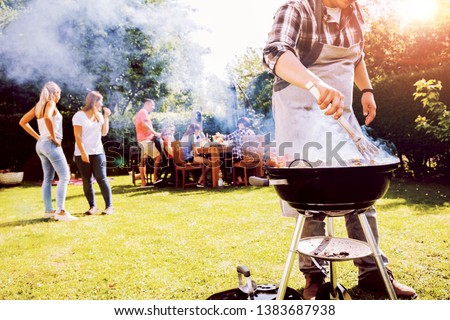 Summer garden bbq party with grill and people in background