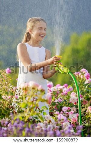 Summer garden, watering - beautiful  girl watering roses with garden hose in the garden