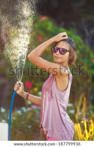 Summer garden, watering - beautiful woman watering roses with garden hose in blooming summer garden