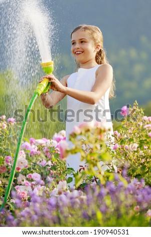 Summer garden, watering -  girl has fun watering roses with garden hose