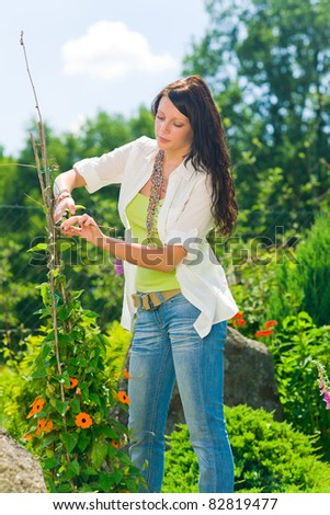 Summer gardening young woman cutting flower on beautiful sunny day