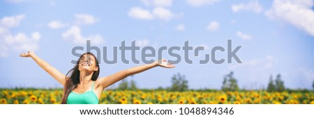 Summer girl happy in sunflower flower field for spring. Cheerful multiracial Asian Caucasian young woman joyful with arms raised up. Panoramic landscape banner. #1048894346