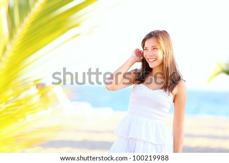Summer girl on beach. Cute young woman model standing happy and lovely in white sundress on tropical beach. Adorable mixed race Asian / Caucasian eurasian woman in her twenties.