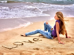 Summer girl sea.  Teenager writing love  on sand.