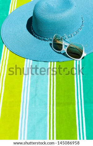Summer hat with sunglasses on a beach towel.