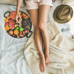 Summer healthy raw vegan clean eating breakfast in bed concept. Young girl wearing pastel colored home clothes taking fig from tray full of fresh seasonal fruit. Top view, square crop