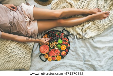Summer healthy raw vegan clean eating breakfast in bed concept. Young girl wearing pastel colored home clothes taking fruit from tray full of fresh seasonal fruit. Top view, copy space