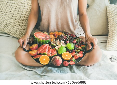 Summer healthy raw vegan clean eating breakfast in bed concept. Young girl wearing pastel colored home clothes sitting and holding tray full of fresh seasonal fruit