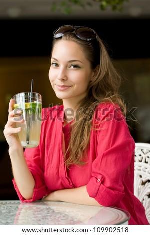Summer heat refreshment, gorgeous young brunette drinking lemonade.