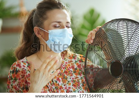 Summer heat. sad middle aged woman in floral blouse with electric fan and medical mask suffering from summer heat in the modern living room in sunny hot summer day.