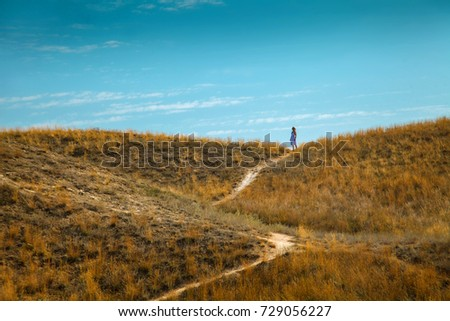 Summer. Heat. Steppe. A woman walks along the path. Loneliness.
