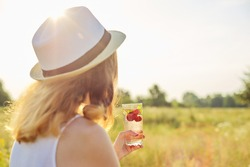 Summer, heat, thirst. Woman in hat with her back with glass of homemade refreshing natural strawberry mint drink, copy space summer sunset meadow nature