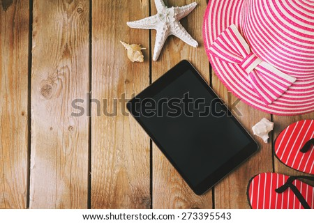 Summer holiday background with digital tablet on wooden table