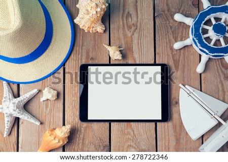 Summer holiday background with digital tablet on wooden table. View from above