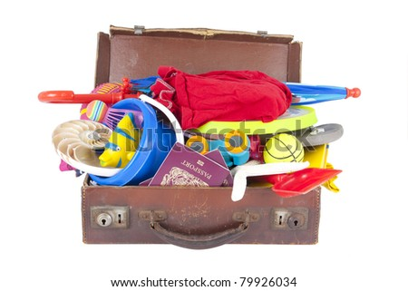 summer holiday beach and vacation suitcase packed full of clothes and toys