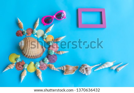 Summer  holiday  concept  setting  with  colorful  seashells,sunglasses  and  wooden  picture  frame  on  blue  background