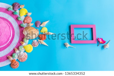 Summer  holiday  concept  setting  with  straw  hat,colorful  seashells  and  wooden  picture  frame  on  blue  background