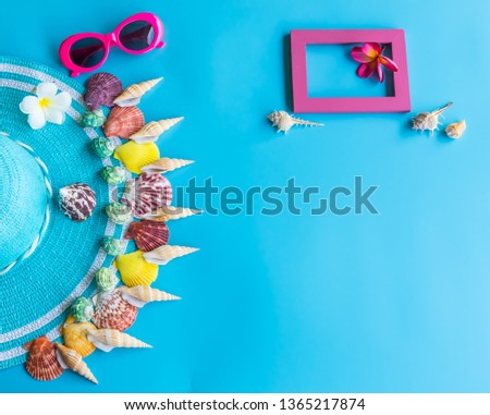 Summer  holiday  concept  setting  with  straw  hat,colorful  seashells,sunglasses  and  wooden  picture  frame  on  blue  background