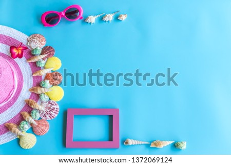 Summer  holiday  concept  setting  with  straw  hat,colorful  seashells,sunglassess  and  wooden  picture  frame on  blue  background
