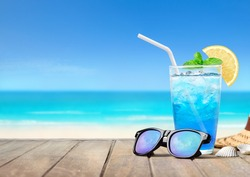 Summer holiday concept. Sunglasses with blue hawaii soda cocktail on wooden table with blur white beach and blue sky background.