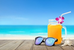 Summer holiday concept. Sunglasses with glass of orange juice on wooden table with blur white beach and blue sky background.