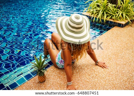 Summer holiday fashion concept - suntanned young woman relaxing near swimming pool with pineapple, shot from above. Wearing wide brimmed hat with stripes, stylish high waist swimsuit. Enjoying suntan #648807451