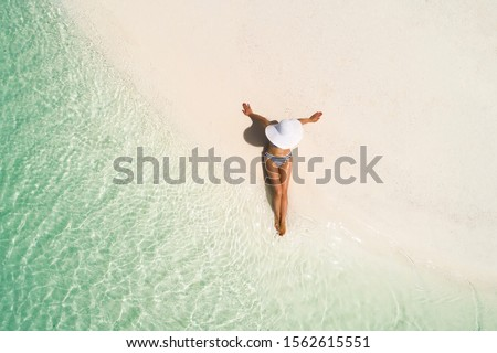 Summer holiday fashion concept - tanning girl wearing sun hat at the beach on a white sand shot from above.Top view from drone. Aerial view of slim woman sunbathing lying on a beach in Maldives.