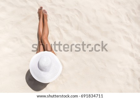 Summer holiday fashion concept - tanning woman wearing sun hat at the beach on a white sand shot from above #691834711