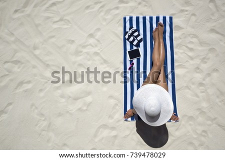 Summer holiday fashion concept - tanning woman wearing sun hat at the beach on a white sand shot from above #739478029