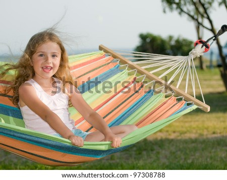 Summer holiday - lovely girl in colorful hammock