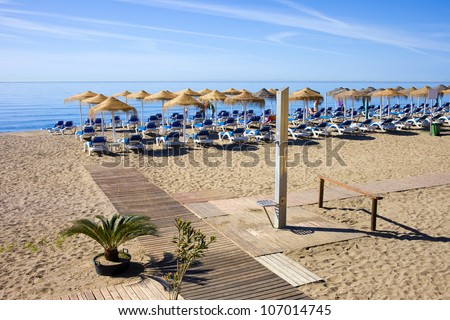 Summer holiday scenery, sandy beach by the blue sea, deckchairs, wooden path and a shower in Marbella resort on Costa del Sol in Spain.