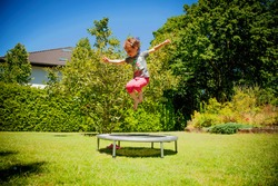 Summer holiday, sport, rest, happy childhood concept. Little cute child girl having fun outdoors and she jumping on a trampoline. Horizontal image.