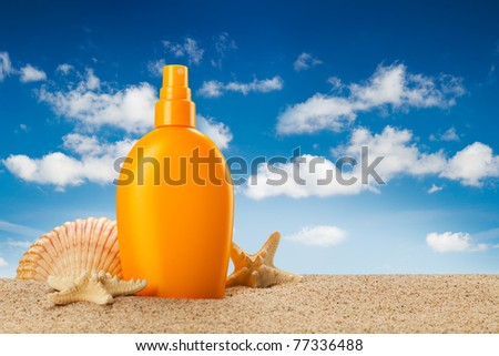 Summer holiday - suntan oil on beach