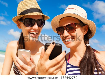 Summer holiday, technology and beach concept. Girls using smart phone on the beach.