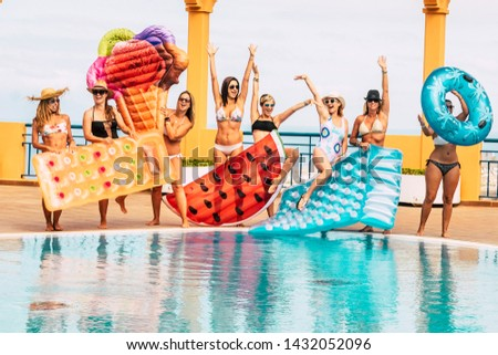Summer holiday vacation at the pool - travel and enjoy the friendship for young beautiful people - group of women in bikini have fun with coloured trendy lilos inflatables - enjoying outdoor together
