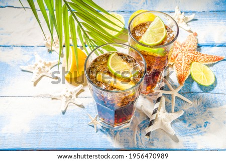 Summer holiday vacation tropical background with iced beverages. Cuba Libre, long island iced tea cocktail with strong alcohol, cola, lime, crushed ice, tropical background with starfish, palm leaves  Photo stock ©