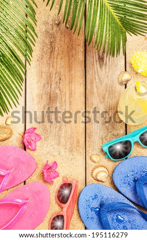 Summer holiday (vacation) tropical beach background layout with free text space. Palm tree leaves, sand, exotic flowers, sunglasses and flip flops on vintage wood - poster design.