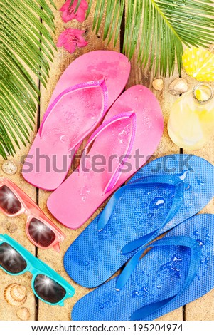 Summer holiday (vacation) tropical beach from above - palm tree leaves, exotic flowers, sunglasses and flip flops on sand.