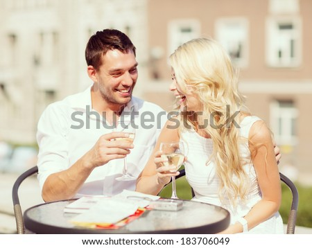 summer holidays and dating concept couple drinking wine in cafe in the city