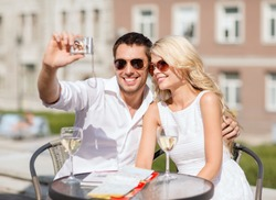 summer holidays and dating concept - couple taking selfie in cafe in the city