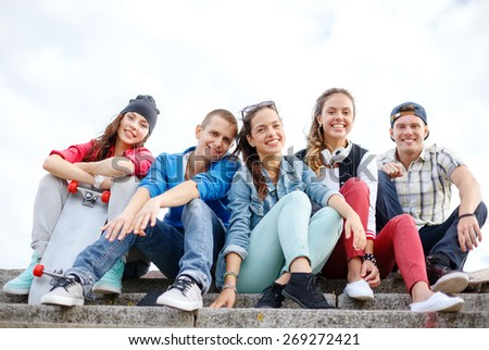 Shutterstock summer holidays and teenage concept - group of smiling teenagers hanging outside