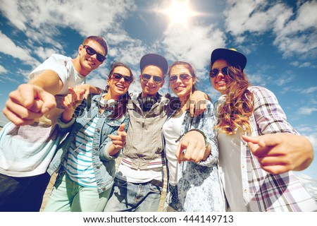 summer holidays and teenage concept - group of smiling teenagers in sunglasses hanging outside pointing finger at you
