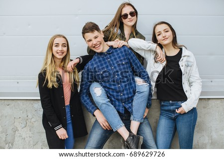summer holidays and teenage concept - group of smiling teenagers with skateboard hanging out outside #689629726