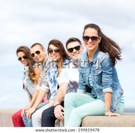 summer holidays and teenage concept - group of teenagers hanging out outside
